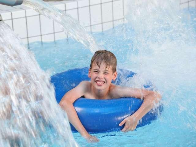 Dreng i badering under vandfaldet i Campusbad i Flensborg