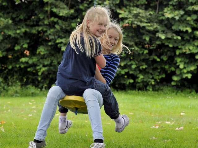 To feriebørn fra Sydslesvig og Danmark gynger sammen i haven under et ferieophold med feriebarn.dk