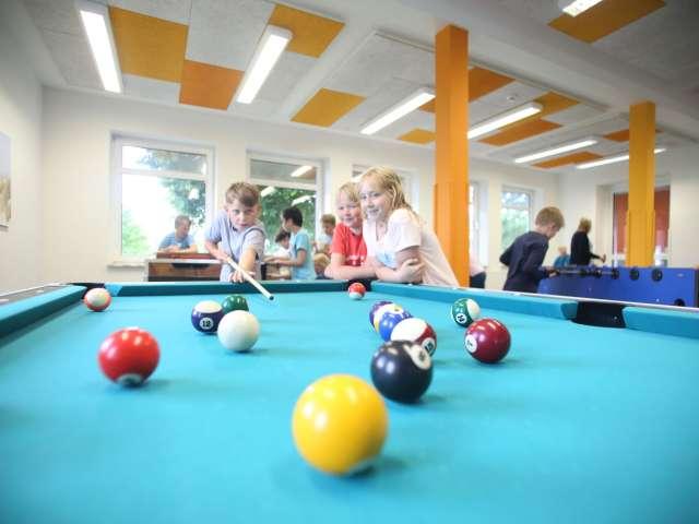 Børn spiller billard og bordfodbold på vandrehjemmet i Frederiksstad