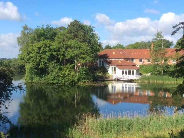 Hovedbygningen af Jaruplund Højskole ved Flensborg med søen i forgrunden