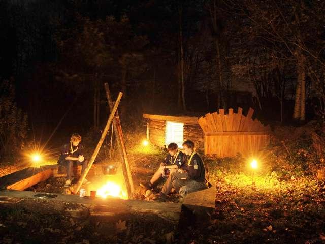 Spejdere hygger omkring lejrbålet om aftenen på Spejdergården Tydal i Eggebæk