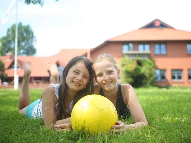 To piger ligger i græsset med en fodbold i hænderne på vandrehjemmet i Tønning.