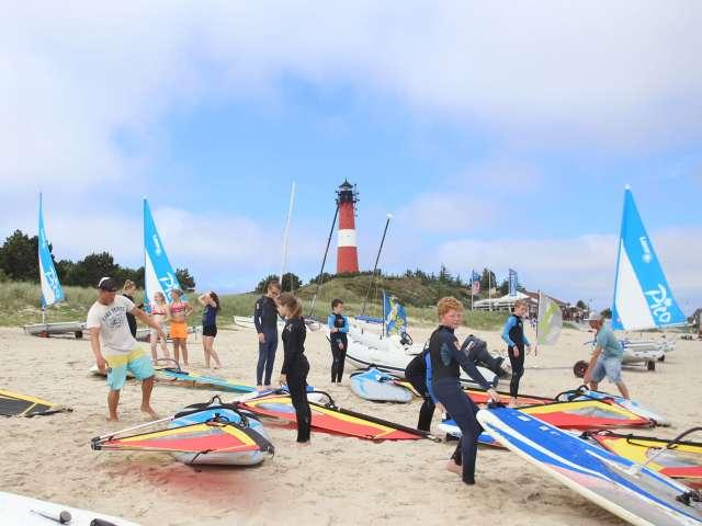 Unge gør klar til windsurfing på stranden på vandrehjemmet i Hørnum på Sild