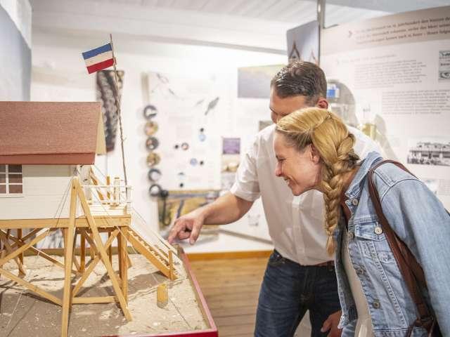Gæster på Museum Landschaft Eiderstedt beundrer modeller af pælebygninger