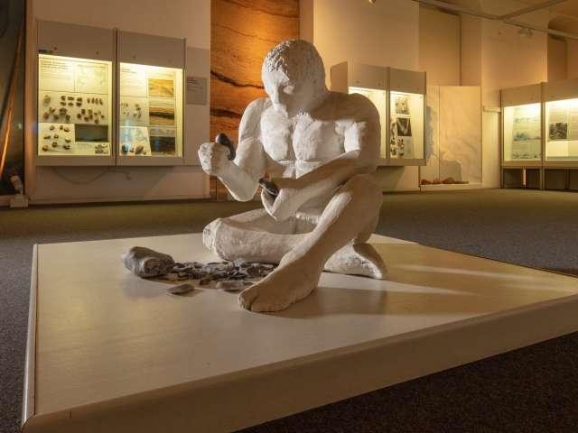 Skulptur af mennesker der prøver at frembringe gnister ved hjælp af flintesten på Museet for Arkæologi på Gottorp Slot i Slesvig