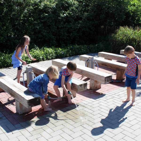 Børn renser fødderne efter besøget i Barfusspark Schwackendorf