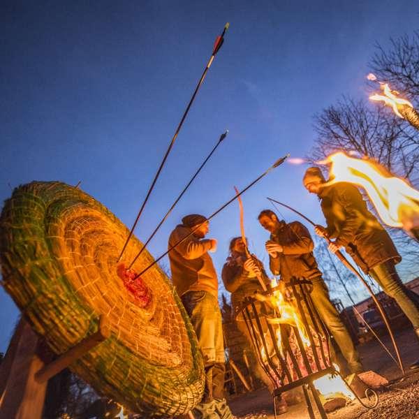 Bueskydning mellem fakler og ved lejrbålet om aftenen i Hochseilgarten Altenhof