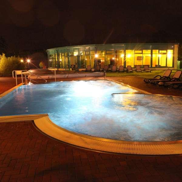 Det belyste udendørsbassin om natten med svømmehallen i baggrunden i Campusbad i Flensborg