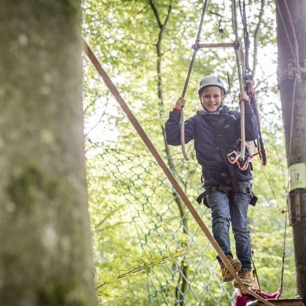 Dreng med hjelm og klatreudstyr på line mellem to træer i Hochseilgarten Altenhof