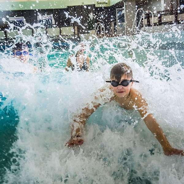 Dreng med svømmebriller leger i bølgerne i bølgebassinnet i badelandet Dünentherme i Sankt Peter-Ording