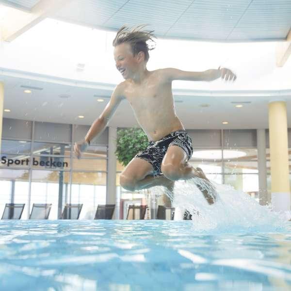 Dreng springer ud i vandet i forlystelsesbadet Sylter Welle i Vesterland på Sild.