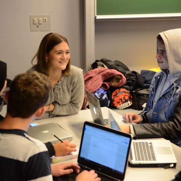 Elever sidder med deres bærbare og arbejder sammen under et besøg af Elevambassadørerne på en skole i Danmark.