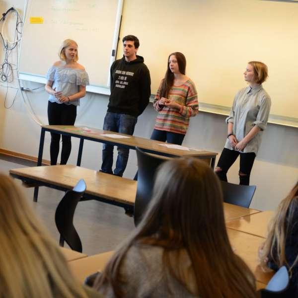 En gruppe af Grænseforeningens Elevambassadører står foran tavlen i en klasse med danske skoleelever.
