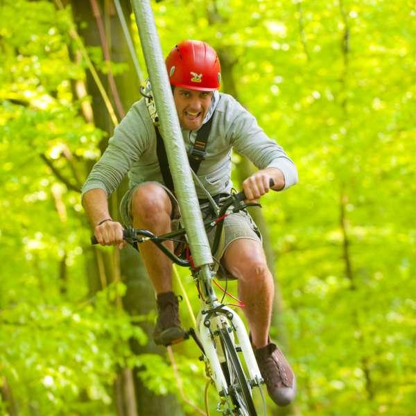 En mand cykler på line mellem trætoppene i Hochseilgarten Altenhof