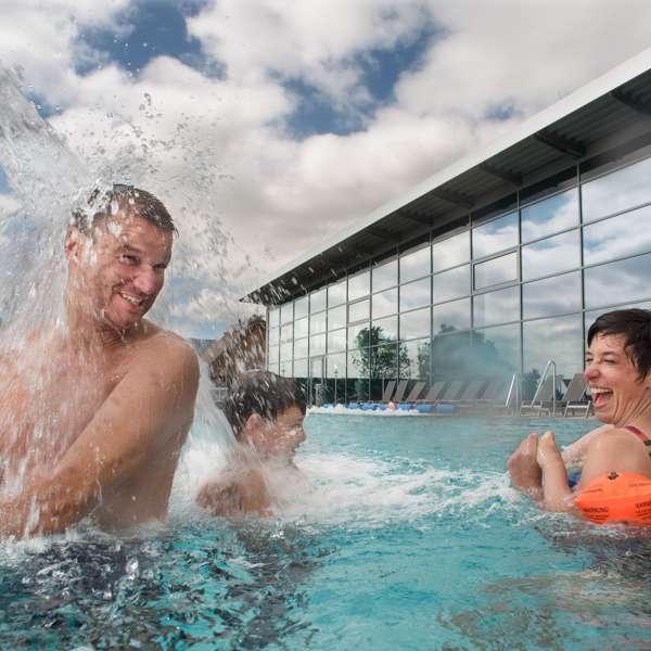 Familie leger i udendørsbassinnet i oplevelsesbadet Entdeckerbad på Ostsee Resort Damp