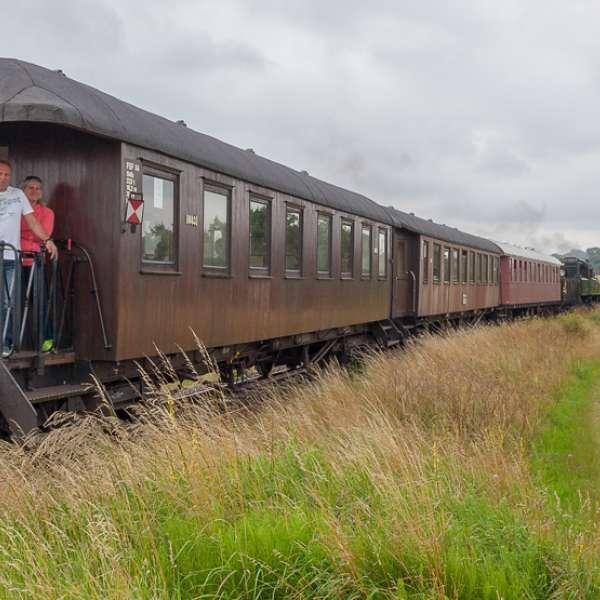 Familie nyder udsigten fra den bagerste vogn af damptoget Angelner Dampfeisenbahn