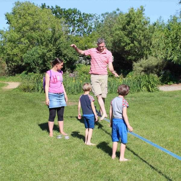 Far balancerer på slackline i Barfusspark Schwackendorf mens mor og børnene ser på