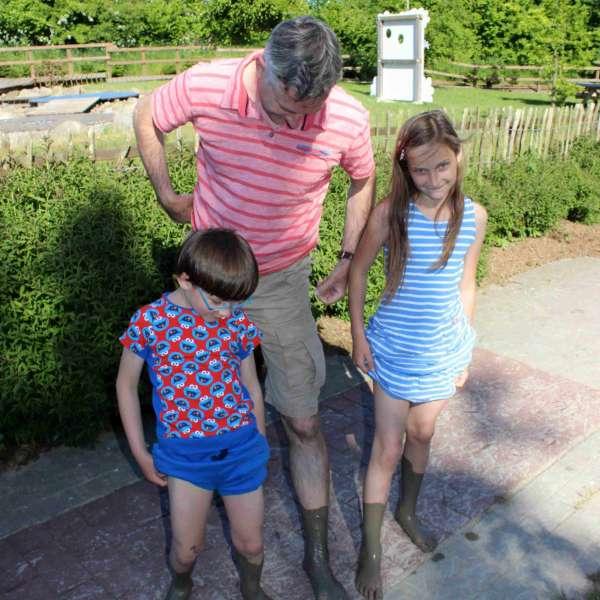 Far og børn med beskidte fødder efter en tur over mosestien i Barfusspark Schwackendorf
