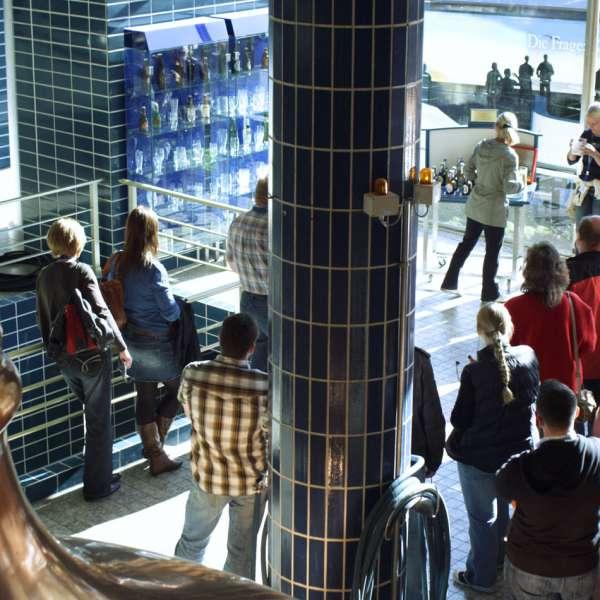 Gruppe lytter til guidens oplæg ved siden af en stor brygkedel.