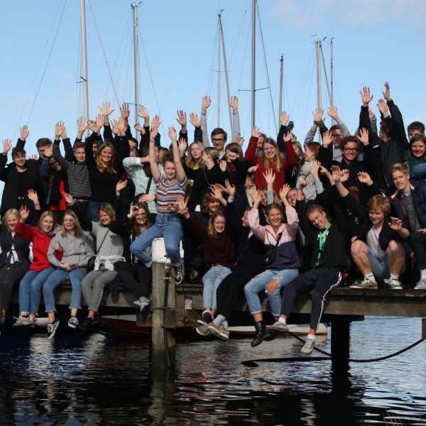 Gruppebillede af Grænseforeningens Elevambassadører på en bro i en lystbådehavn i Sydslesvig