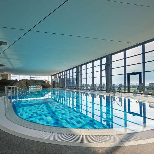 Indendørsbassinnet med udsigt over strand og hav i oplevelsesbadet Entdeckerbad på Ostsee Resort Damp