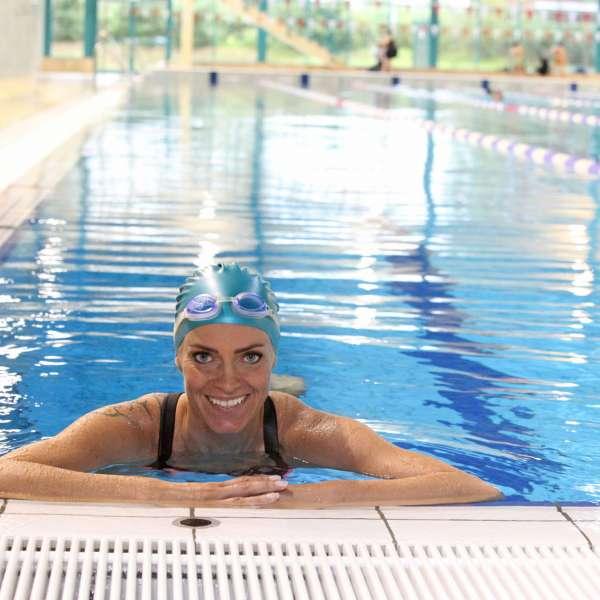 Kvinde med badehætte og svømmebriller i sportsbassinnet i Campusbad i Flensborg