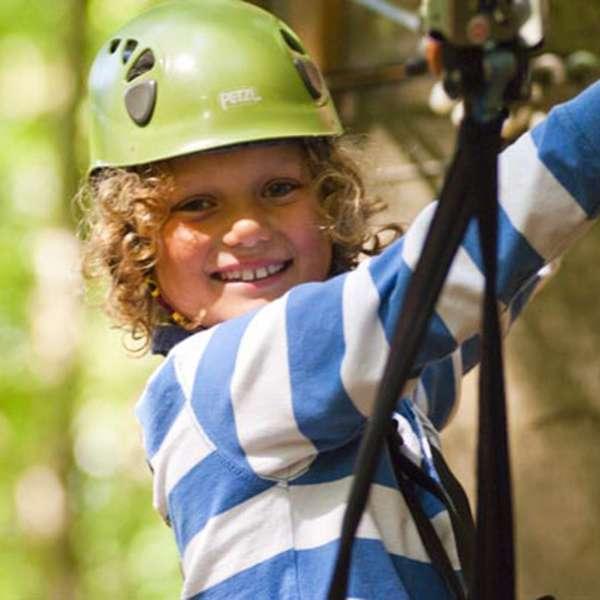 Lille dreng med hjelm og klatreudstyr klatrer i træerne i Hochseilgarten Altenhof
