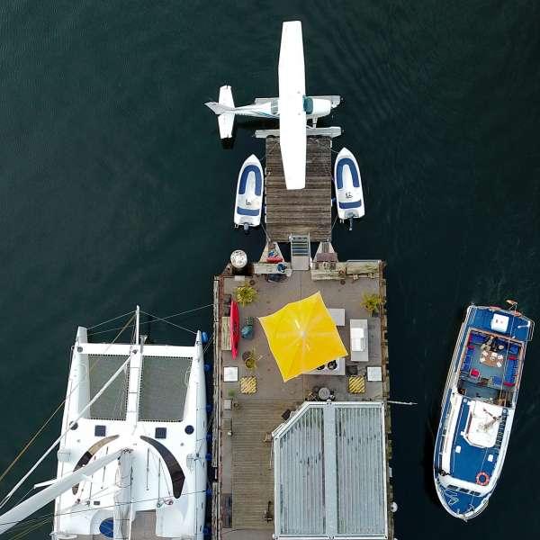 Luftbillede af Fly & Sails anløbsbro i Flensborg Sonwik med sejlkatamaran, turbåd, lejebåde og vandflyet i Flensborg-Sonwik