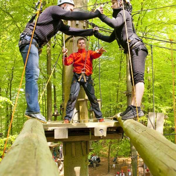 Par balancerer på to bjælker mellem trætoppene i Hochseilgarten Altenhof