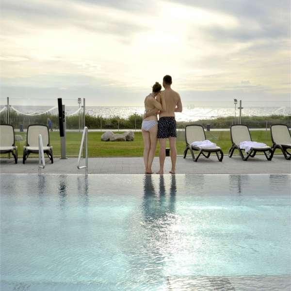 Par nyder solnedgangen under besøget på oplevelsesbadet Entdeckerbad på Ostsee Resort Damp