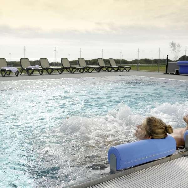 Par slapper af i udendørspoolen under opholdet på oplevelsesbadet Entdeckerbad på Ostsee Resort Damp