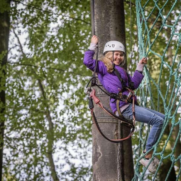 Pige med hjelm og klatreudstyr klatrer op ad et net i Hochseilgarten Altenhof