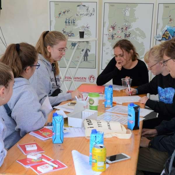 Skoleelever koncentrerer sig om en gruppeopgave under et besøg af Elevambassadørerne på en skole i Danmark.