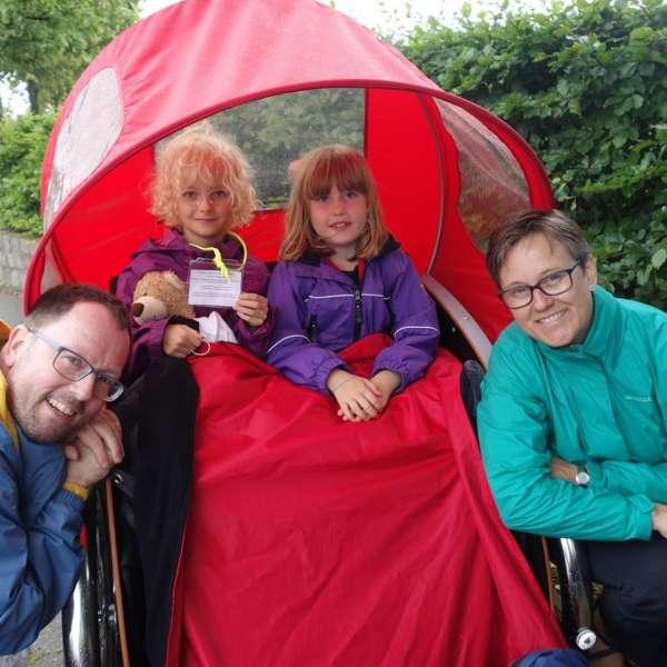 Værtsfamilie med børn på udflugt. Feriebarn og værtsfamiliens barn sidder sammen i cykeltrailer under ferieophold med feriebarn.dk