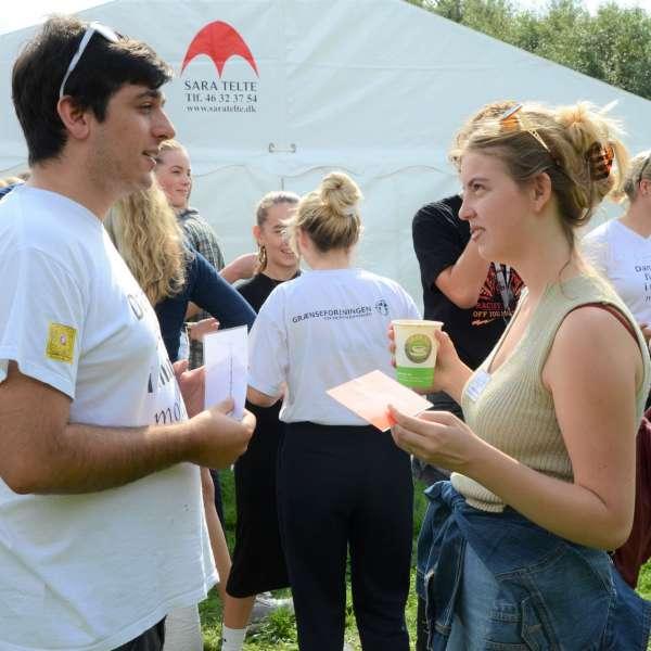 To teenagere står og snakker sammen under et besøg af Grænseforeningens Elevambassadørerne.