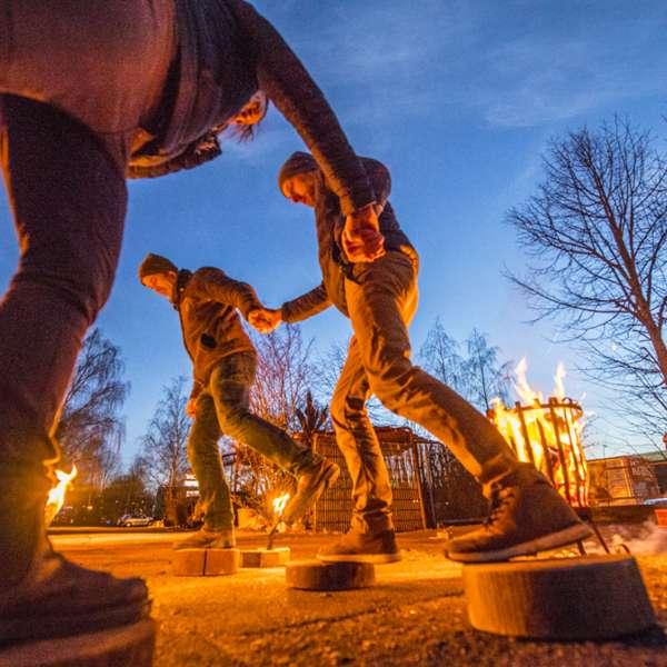 Tre besøgende balancerer på klodser ved lejrbålet i Hochseilgarten Altenhof