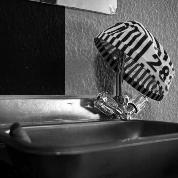 Vaskekumme med en fanges stribede kasket hængende over vandhanen i Mystery House Flensborg