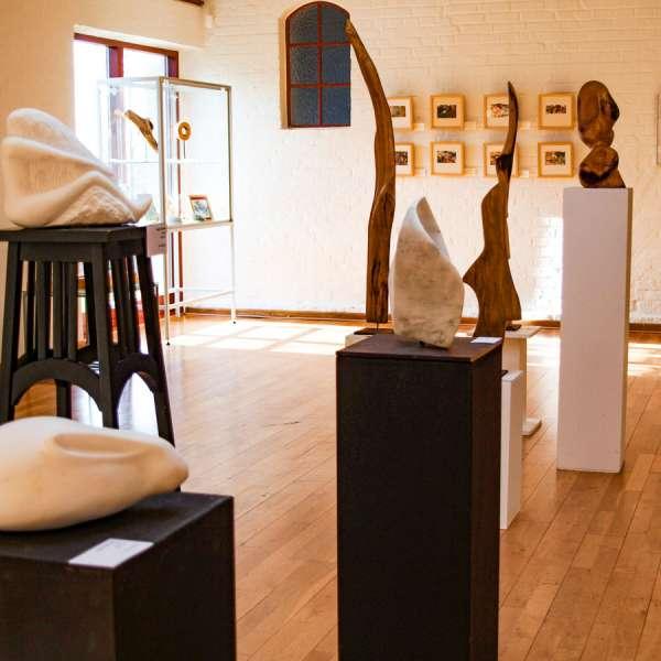 """Skulpturer og andre billeder i baggrunden på udstillingen """"Künstlerfreunde V"""" på Mikkelberg"""