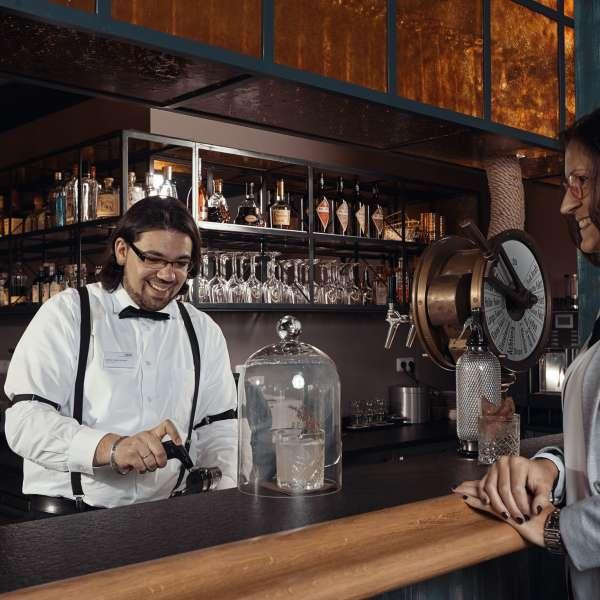 Bartender med hotelgæst på gin- og cocktailbaren Hammaburg på Ostsee Resort Damp
