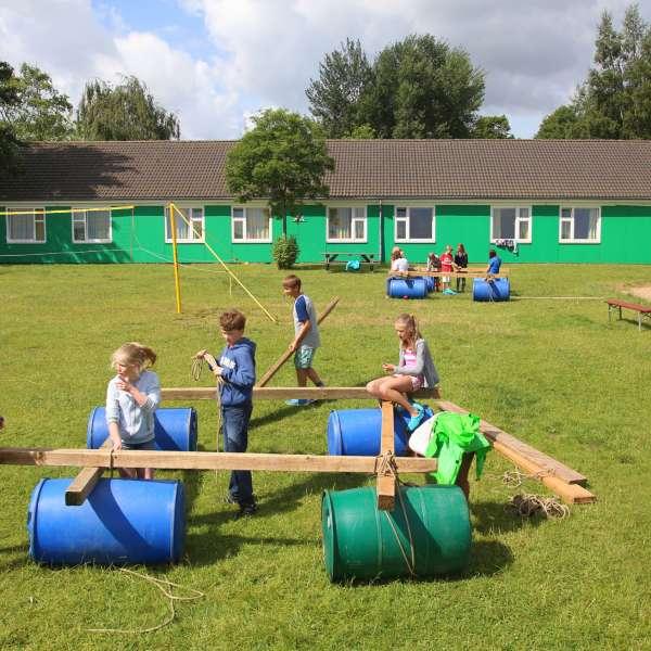 Børn bygger en tømmerflåde på græsplænen på vandrehjemmet i Borgvedel ved Slesvig