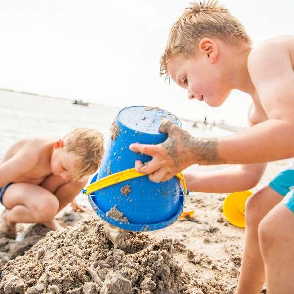Børn bygger et sandslot på stranden ved Ostsee Resort Damp