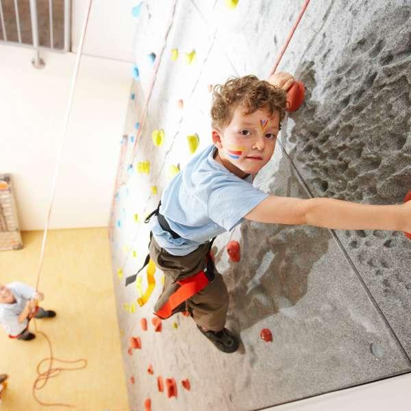 En dreng prøver kræfter med klatrevæggen i klatrehallen på Dorfhotel Sylt i Rantum på Sild.