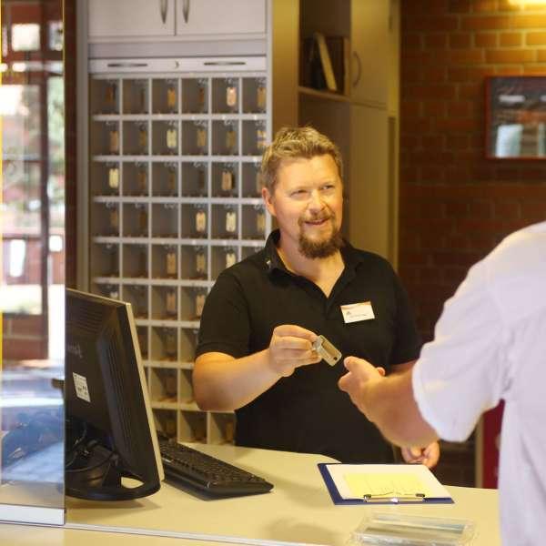 En gæst tager i mod nøglerne til sit værelse i receptionen på vandrehjemmet i Tønning