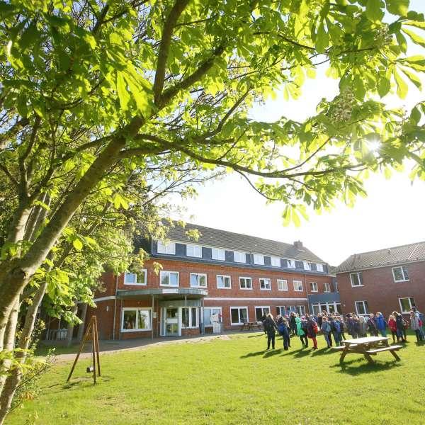 En skoleklasse samles i haven på vandrehjemmet i Vyk på Før