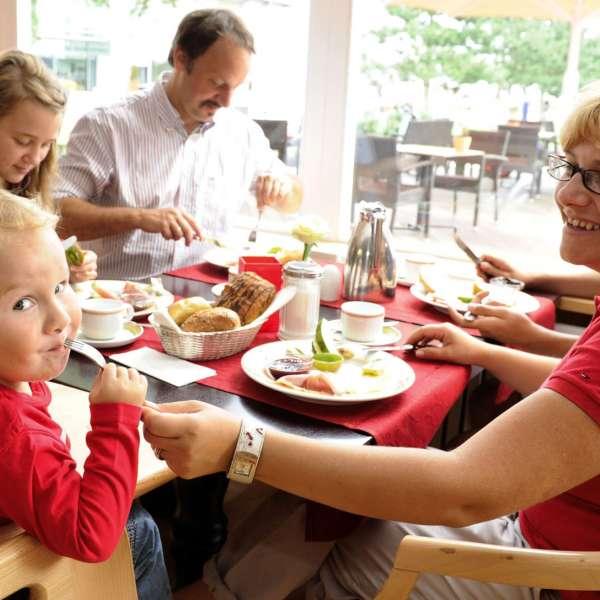 Familie spiser morgenmad på Ostsee Resort Damp