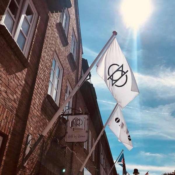 Flag med hotellets logo på hovedbygningen på ONNO Hotel by Norman i Rendsborg