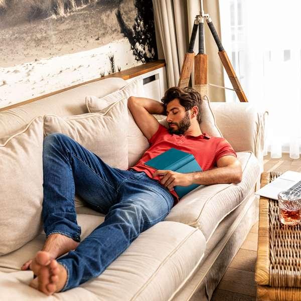 Hotelgæst slapper af på sofaen i sit hotelværelse på Hotel Zweite Heimat i Sankt Peter-Ording