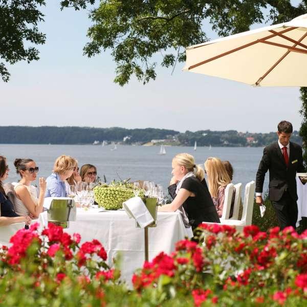 Hotelgæster hygger omkring et fint dækket bord i haven med udsigt over Flensborg Fjord på Vitalhotel Alter Meierhof i Lyksborg