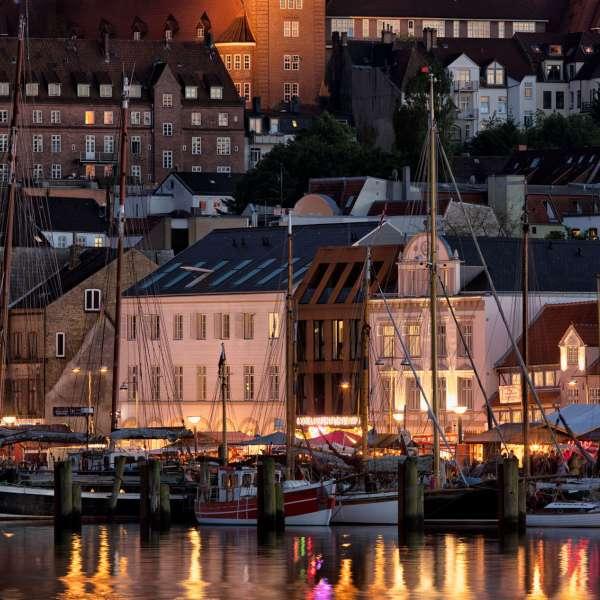 Hovedbygningen af Hotel Hafen Flensburg i Flensborg i aftentimerne set fra den anden side af havnen