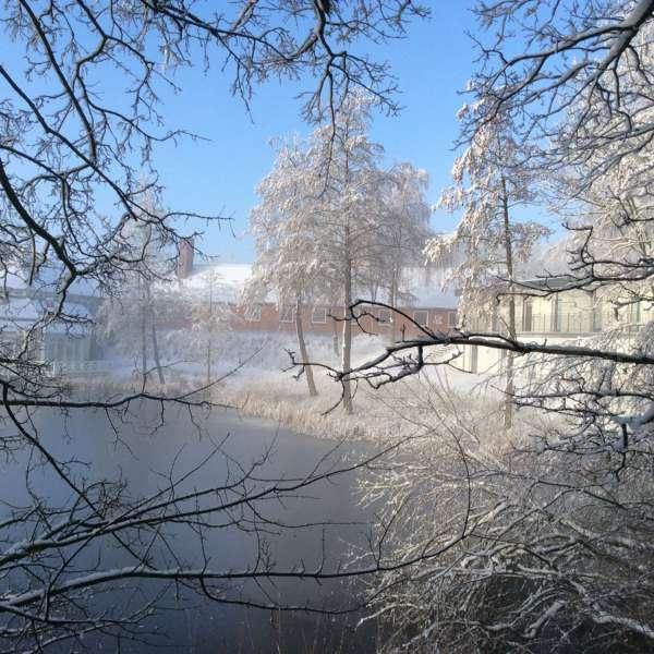 Jaruplund Højskole ved Flensborg i snevejr om vinteren set fra søen